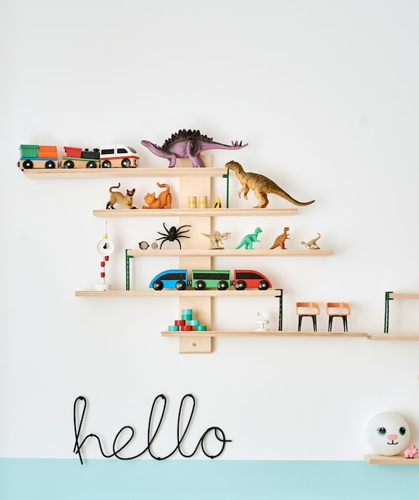 A set of wooden shelves with a display of toys including dinosaurs and trains. Below is a 'hello' sign made of black metal.