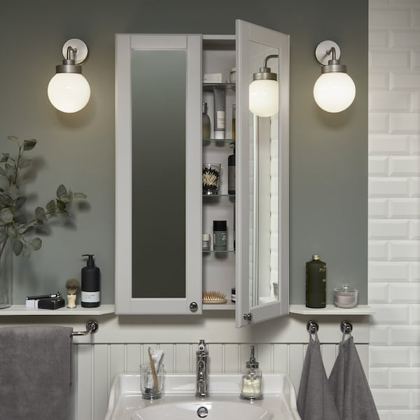 A shallow but high mirror cabinet over a white wash-basin. One door is open, and beauty items are stored inside.