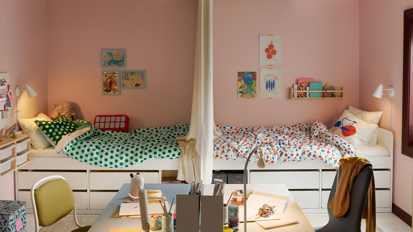 A shared children's bedroom divided in two with the beds facing each other and in the foreground two desks facing each other.