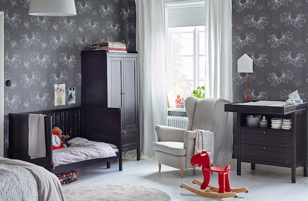 A shared parent and child's room with a SUNDVIK changing table, SUNDVIK crib and SUNDVIK crib against a wall with floral wallpaper.