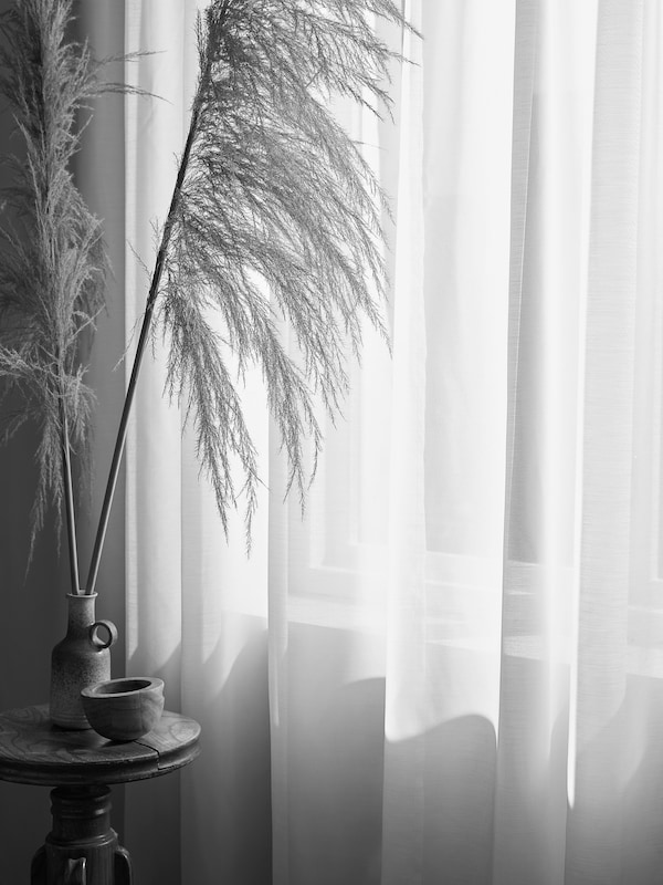 A sheer white curtain billowing in front of a sunny window with a a light brown windowsill.