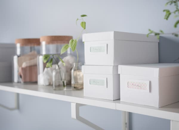 A shelf in white and light wood with boxes and jars for storage.