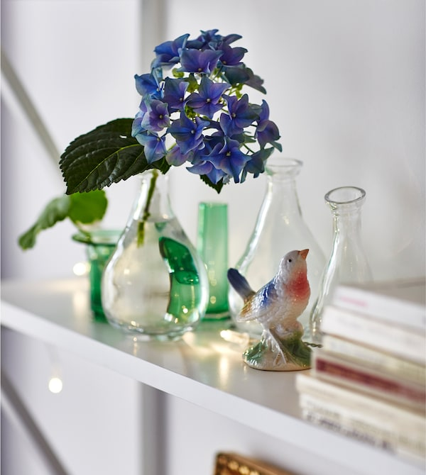 A shelf is decorated with small glass vases and a figurine of a bird.