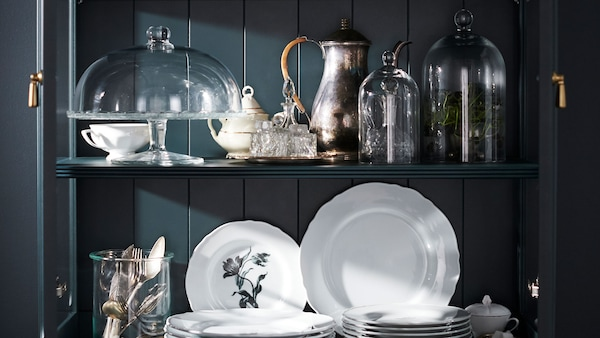 A shelf with attractively arranged china and glass bell jars.