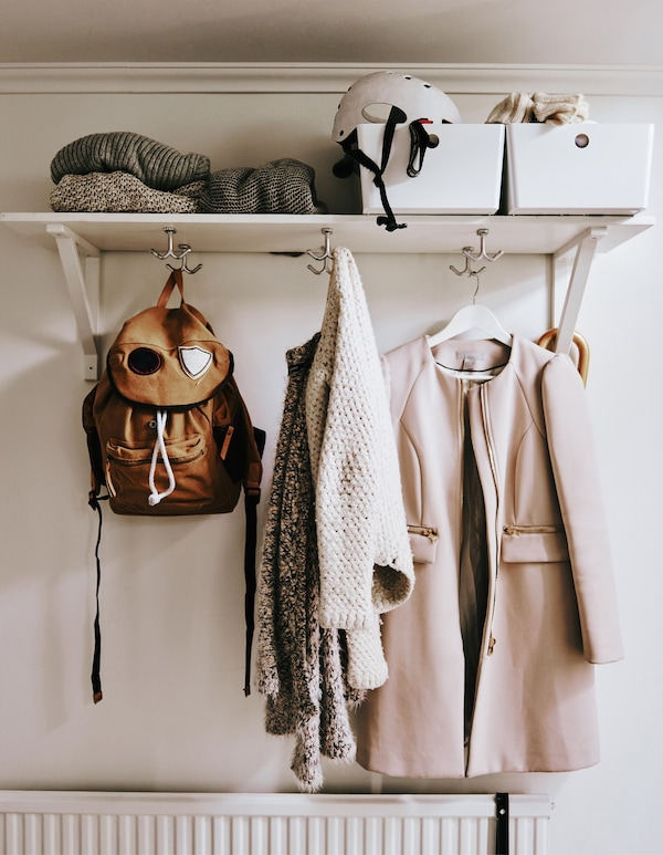 A shelf with boxes on top and hooks underneath.