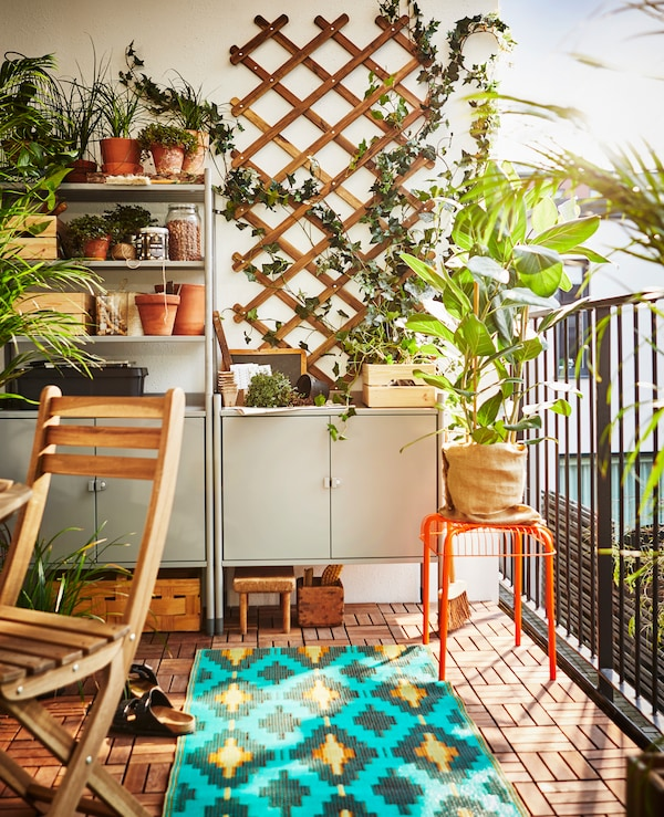 A shelving unit sits on a balcony to create storage and a workspace for gardening.
