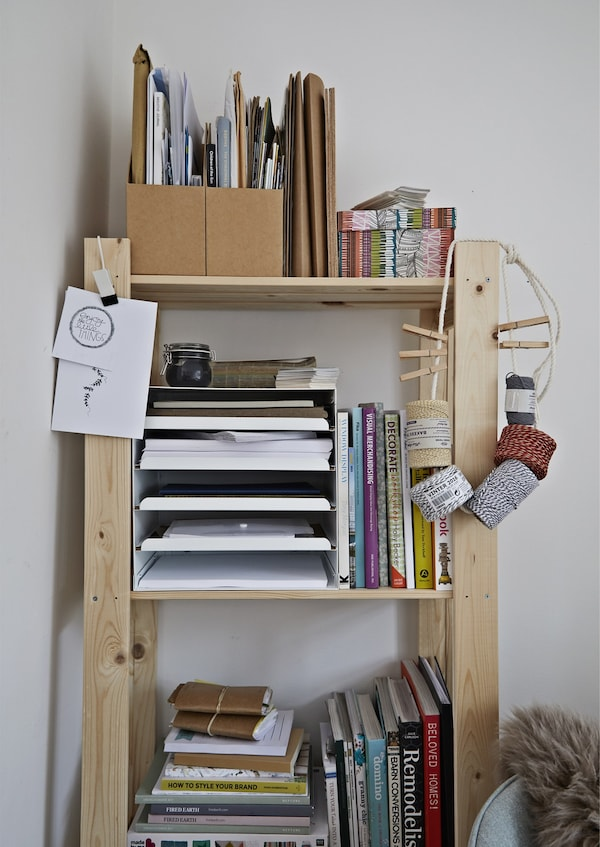 A shelving unit stacked with books and papers.