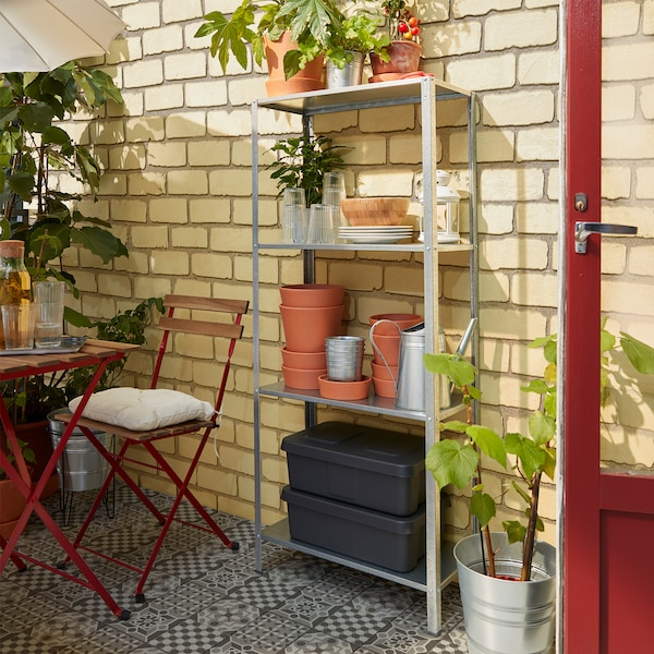 A shelving unit with four shelves where storage boxes, plant pots, plates and glasses stand within easy-reach by a table.