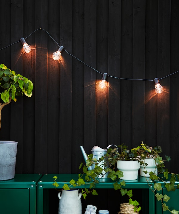 A shimmering lighting chain hanging from a dark brown house wall, lighting up the patio and two green cabinets.