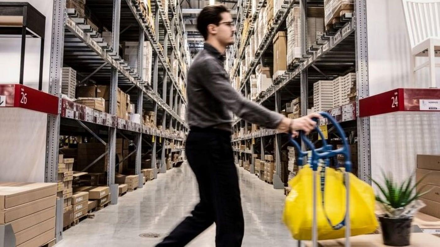 A shopper pushing a cart full of merchandise in an IKEA warehouse.
