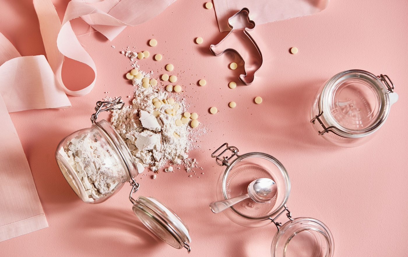 A shot from above of cookie dough ingredients, jars, and cookie cutters on a pink background.
