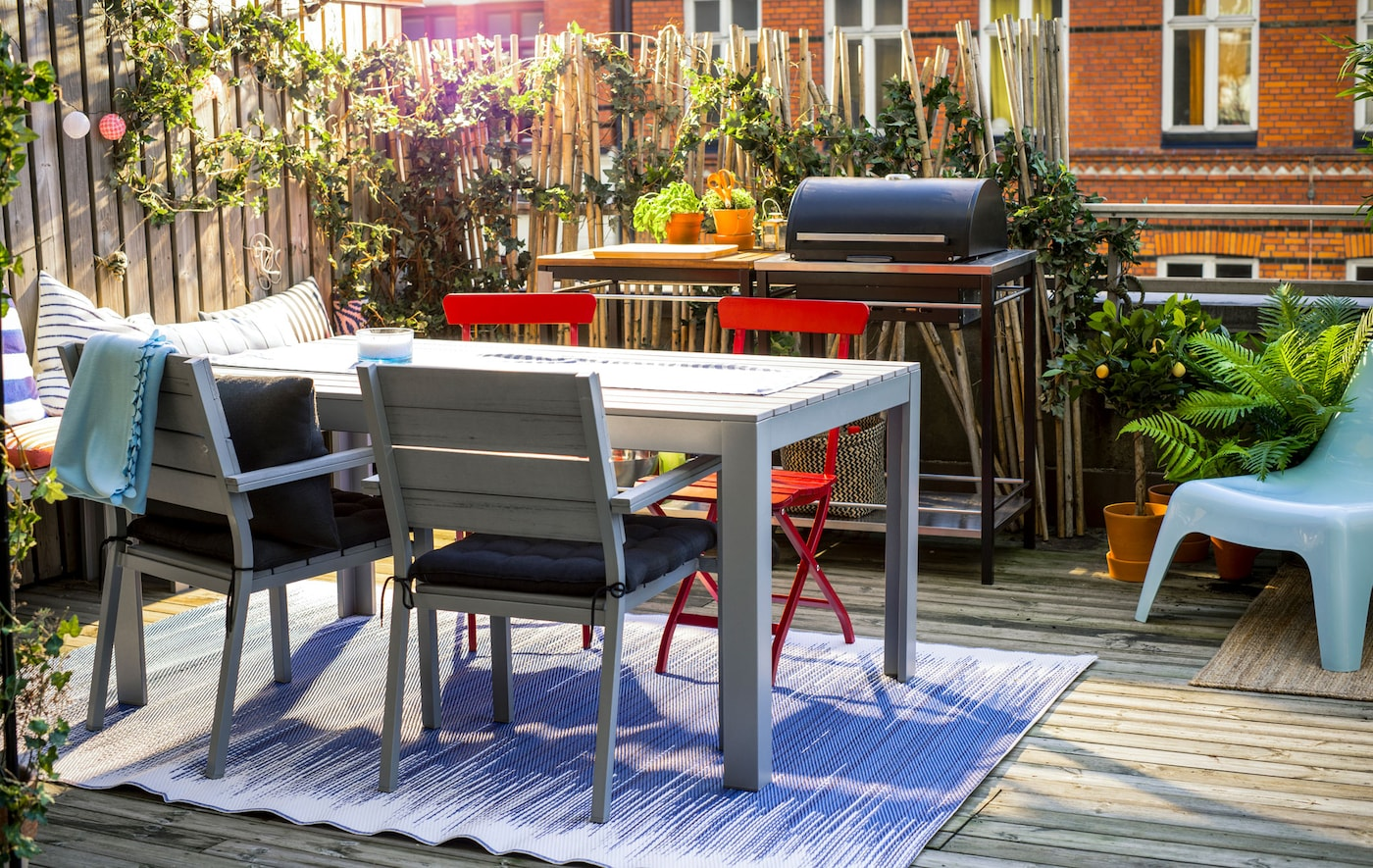 A shot of a balcony with a table and chairs, bench, grill and lots of plants.