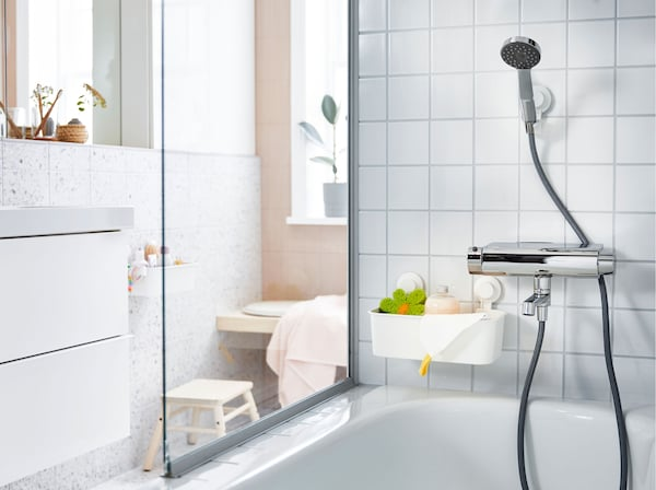 A shower head, above a bath, in a white tiled bathroom, held with an adjustable bracket and suction cup.