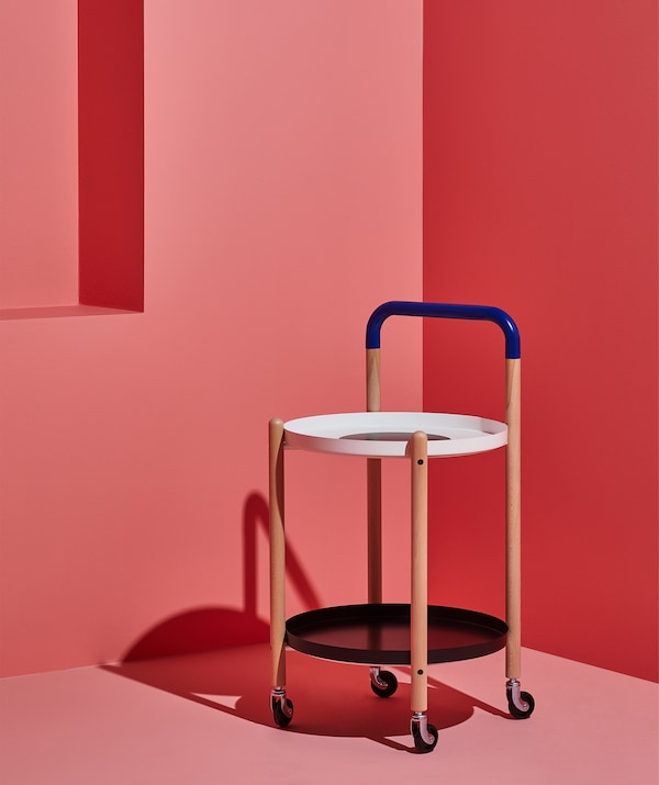 A side table on wheels with wooden frame and a shelf below, in a pink room.