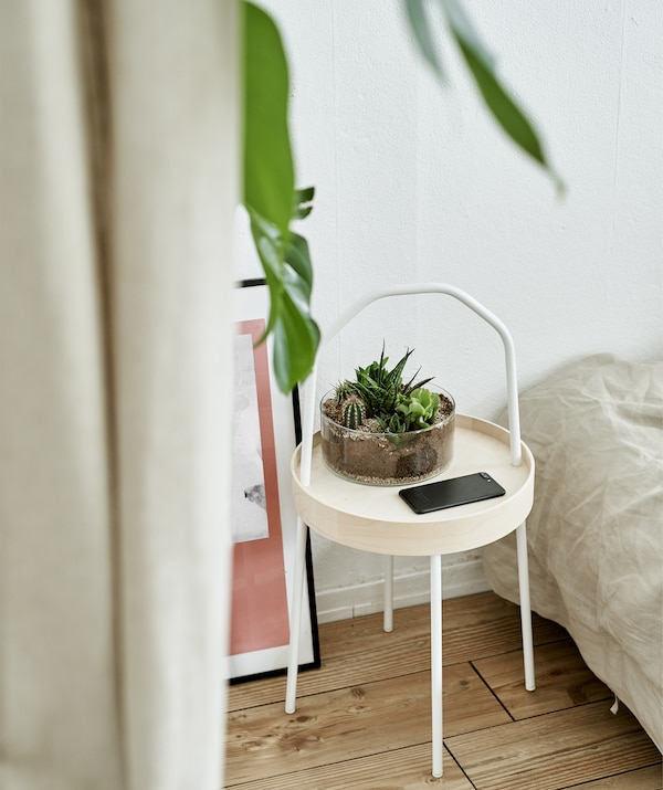 A side table with terrarium in a white bedroom.