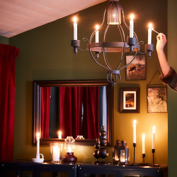 A sideboard with lit candles and a person lighting candles on a chandelier.