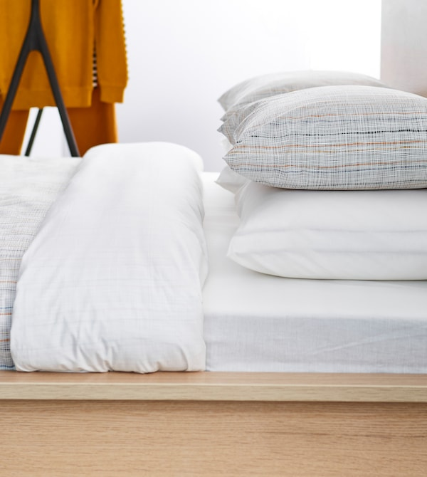 A sideview of a neatly made bed with white linens and simple striped pillows.