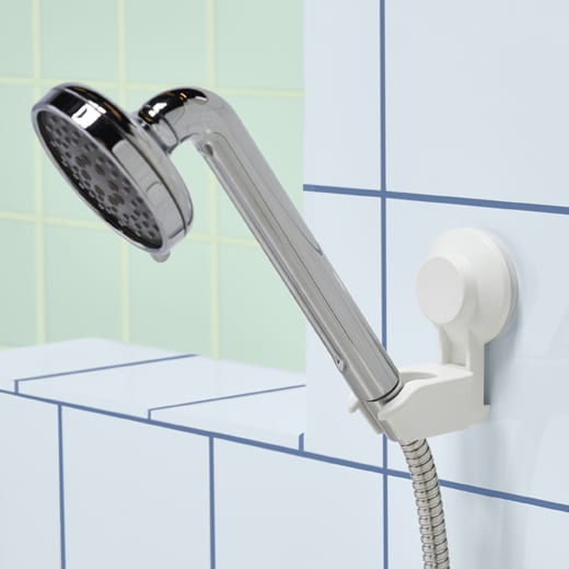 A silver-coloured shower head resting in a suction cup holder on a tiled wall.