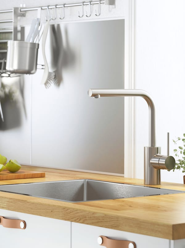 A silver coloured wall panel with a rack, hooks and kitchen utensils hanging from it, a sink and tap on a wooden workop.