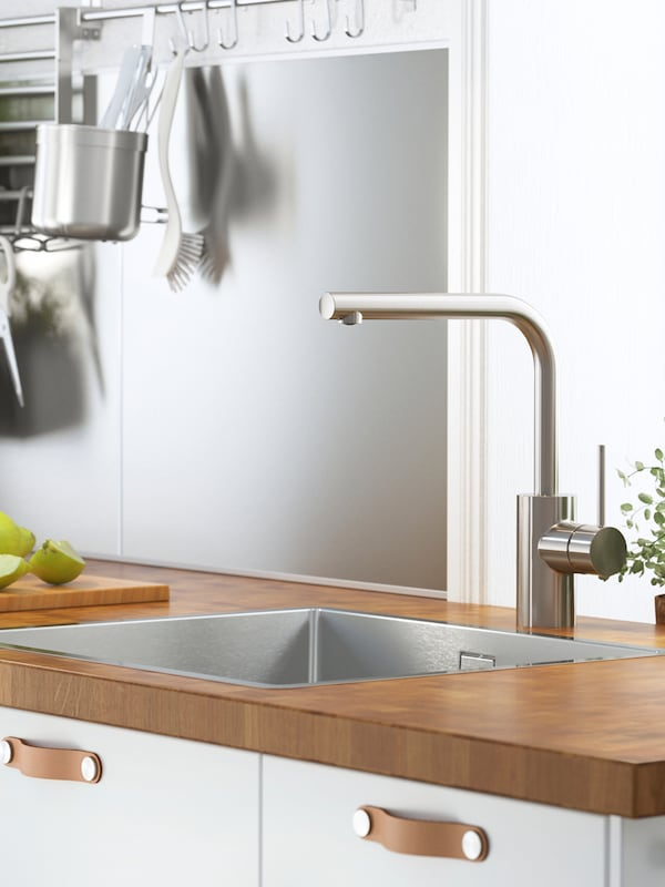 A silver coloured wall panel with a rack, hooks and kitchen utensils hanging from it, a sink and tap on a wooden worktop.