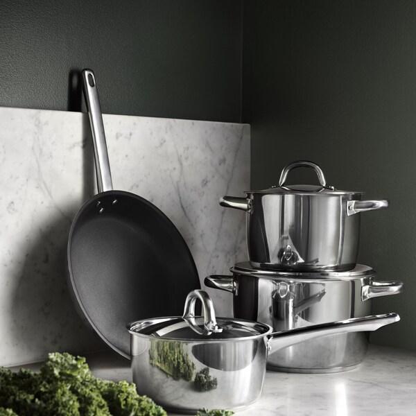 A silver OUMBÄRLIG 7-piece cookware set on a marble kitchen countertop.