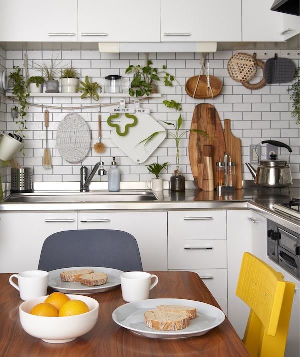 A simple breakfast laid out on a wooden table in a small white kitchen with plants and utensils hung on the walls.