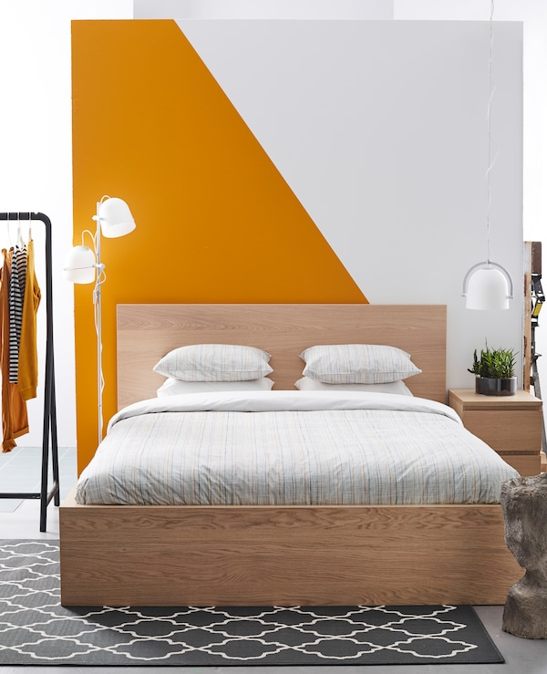A simple, clean bedroom with a graphic orange and white wall.
