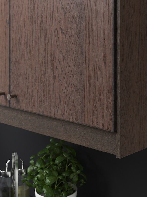 A SINARP cabinet door in dark wood with NYDALA knobs in bronze. There is a pot of basil and condiments underneath.