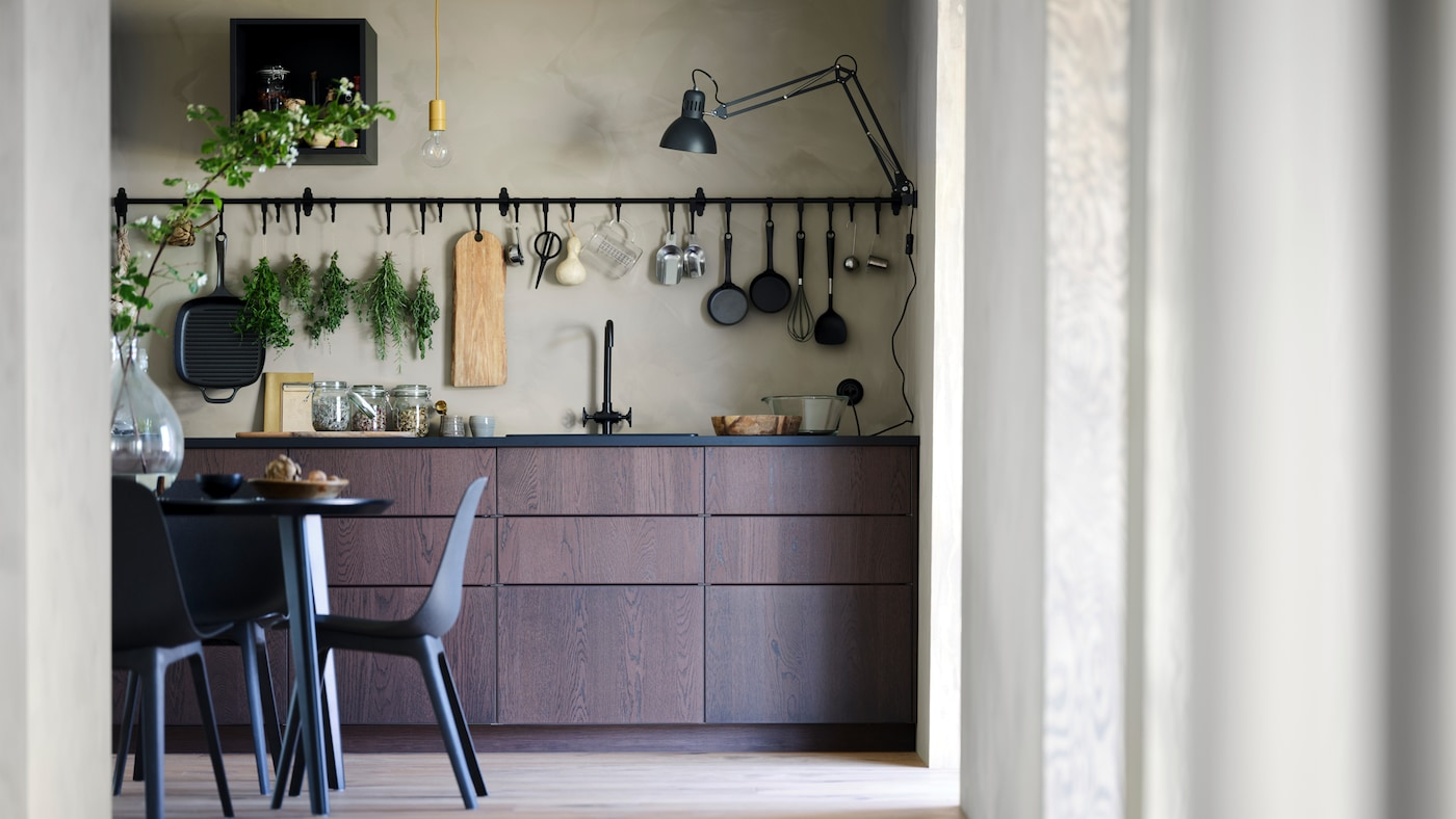 A SINARP kitchen with a table and chairs, and a HULTARP rail and hook hanging on the wall.