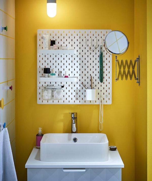 A SKÅDIS pegboard above a white sink unit and a FRÄCK pull out mirror in a small bathroom.