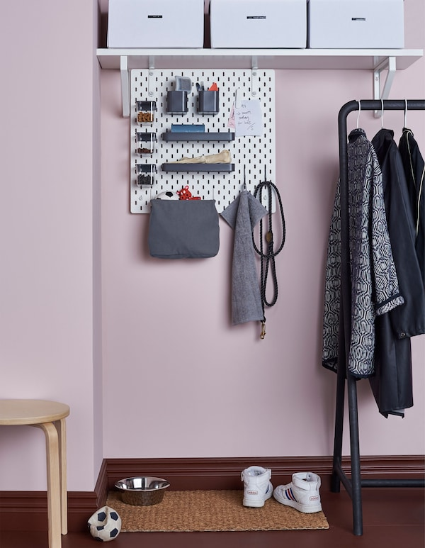A SKÅDIS pegboard connected to a shelf in a hallway with accessories to hold dog-related stuff like toys, leashes, treats and brushes