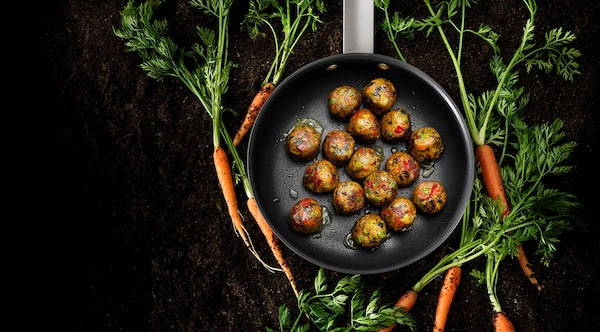 A skillet with ALLEMANSRÄTTEN veggie balls, surrounded by carrots with long, leafy green stems.