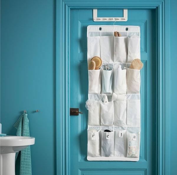 A SKUBB shoe organiser filled with various bathroom accessories, hanging on a door in a turquoise bathroom setting.