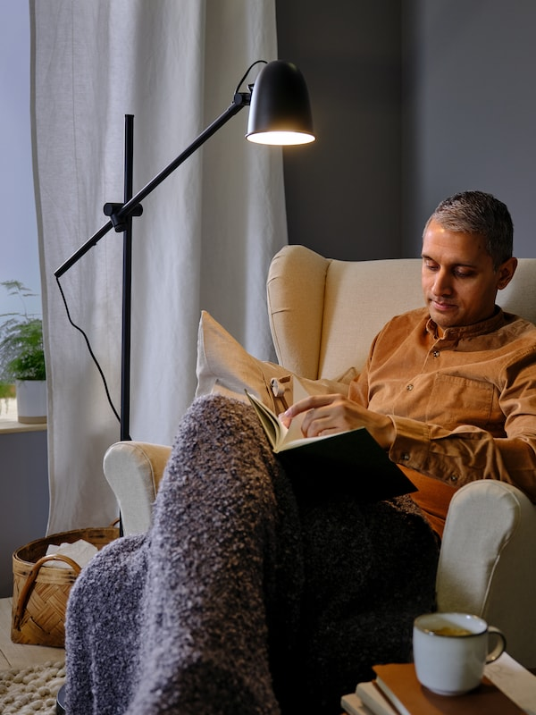 A SKURUP floor lamp provides light for a man who is sitting in a STRANDMON wing chair reading a book.