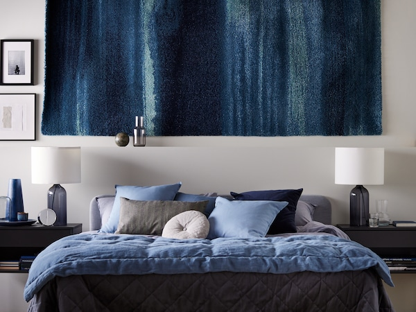 A SLATTUM upholstered bed with dark blue KOPPARBLAD bed linen stands against a wall where a rug is hanging.