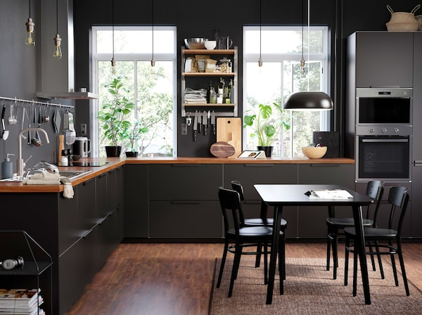 A sleek modern matte black kitchen with open KUNGSFORS suspended rack with shelf and closed IKEA KUNGSBACKA drawers in anthracite with a walnut counter top.