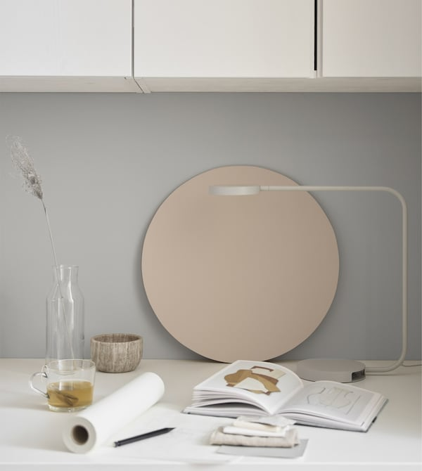 A slender white lamp at a desktop workspace with paper, notebook and a few decorative items.