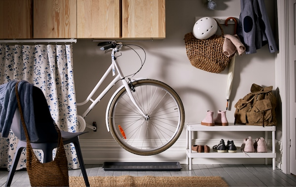 A sliding length of fabric hides a bike hung from a rail underneath wall cabinets in a hallway, shoe mats under the wheels.