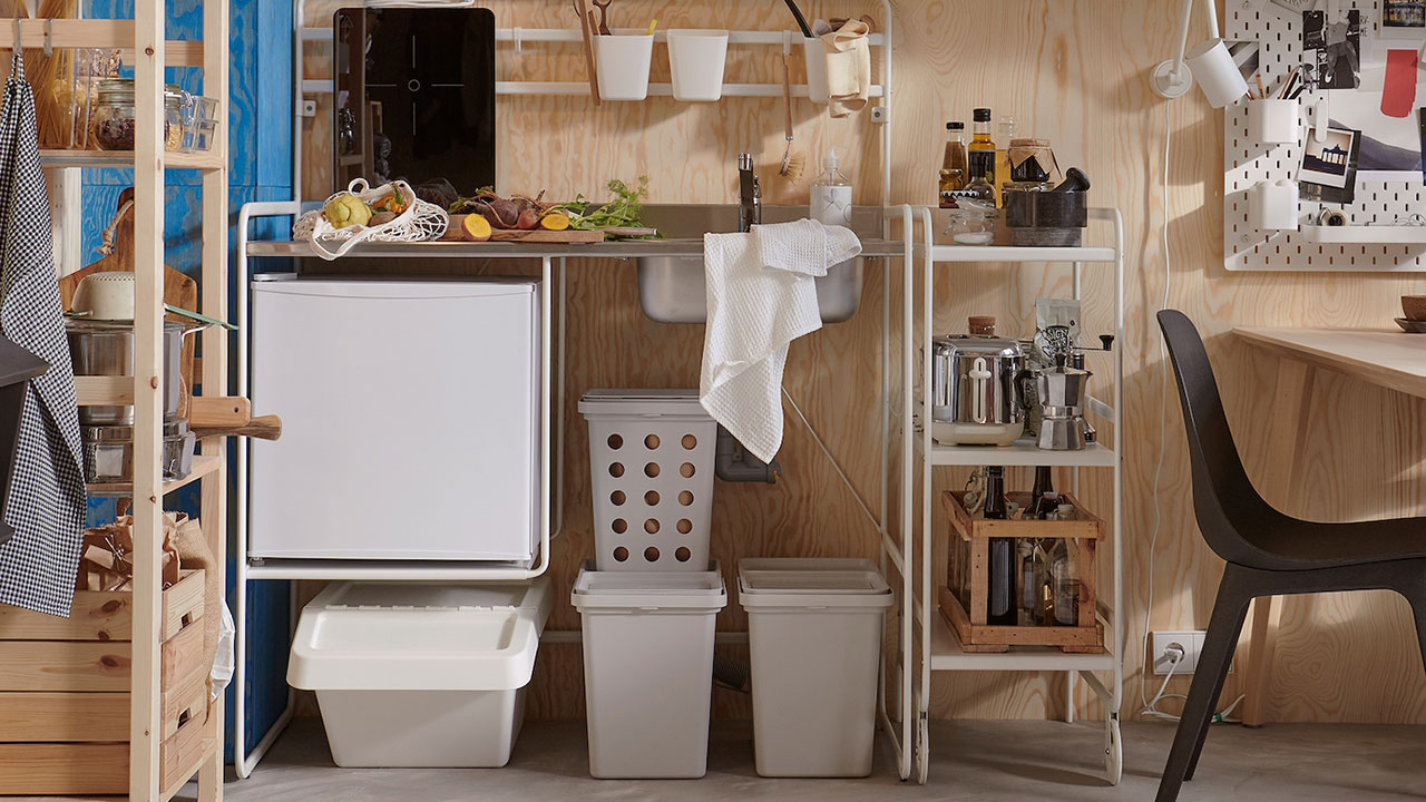 A small and bright kitchen with a SUNNERSTA mini-kitchen, grey waste-sorting bins, a storage system in pine and black chairs.