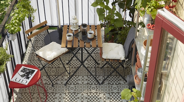 A small balcony space with the TARNO bistro set with coffee and cups on it, greenery and storage in the background.