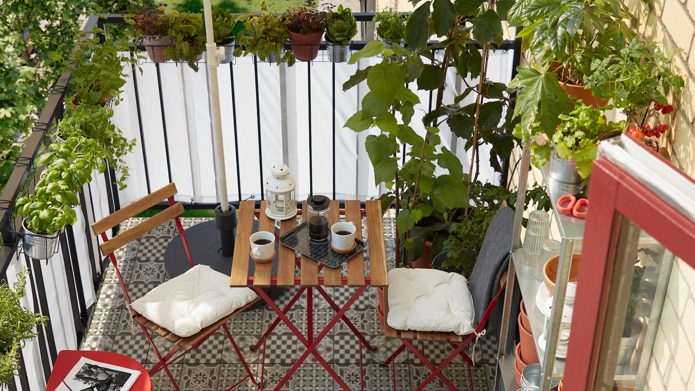 A small balcony with lots of herbs and plants, a shelf with pots, a parasol stand and two chairs and a table.