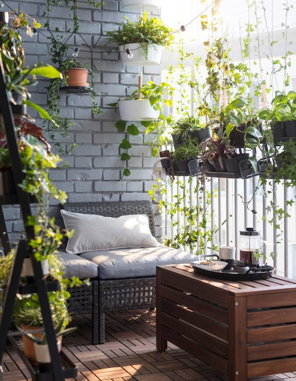 A small balcony with outdoor seating, a low bench, a flower box and plant pots.
