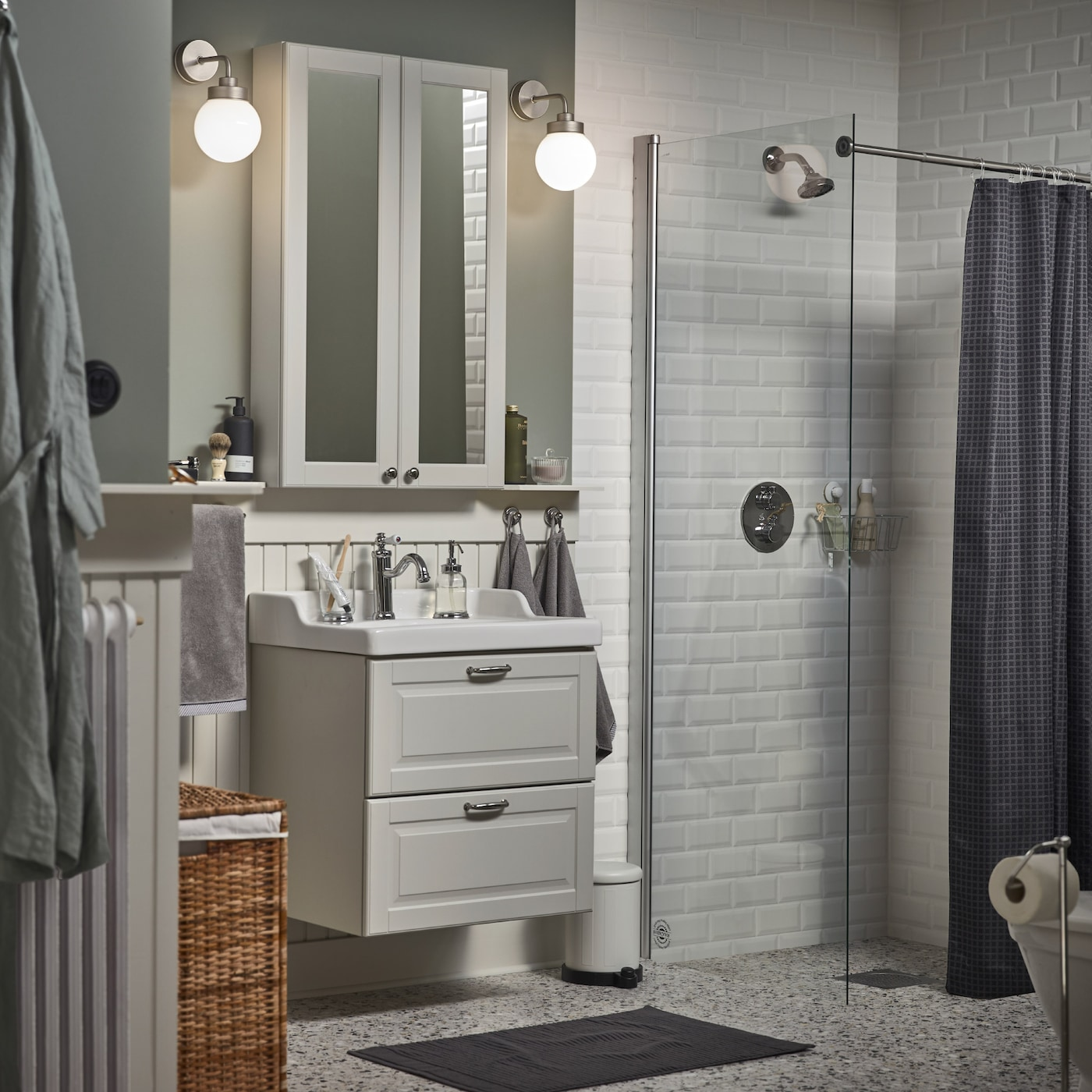 A small bathroom with a white mirror cabinet, a grey wash-stand, a dark grey bath mat and a shower curtain in anthracite.