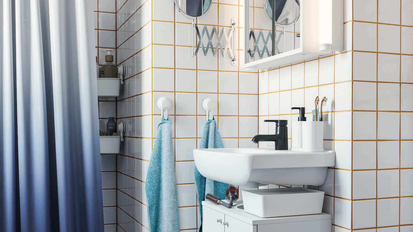 A small bathroom with a white sink cabinet, a black faucet, white tiles with yellow grout, a dark blue shower curtain, hooks with towels.