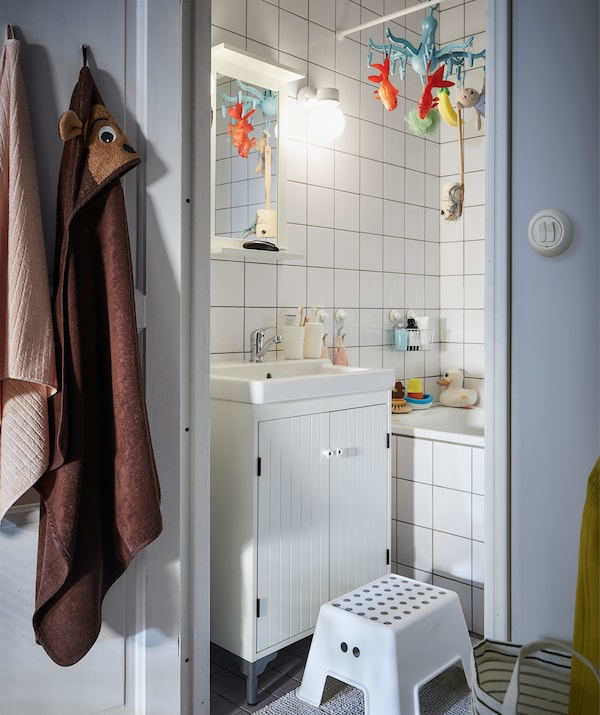 A small bathroom with white tiles and a stool in front of a white vanity unit.