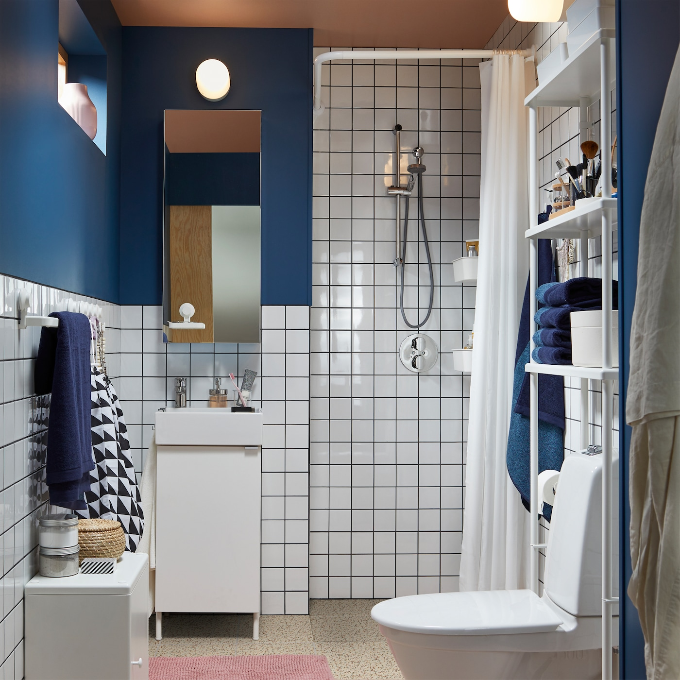 A small bathroom with white tiles and dark blue walls includes a shower, bathroom vanity, mirror cabinet, and blue towels.
