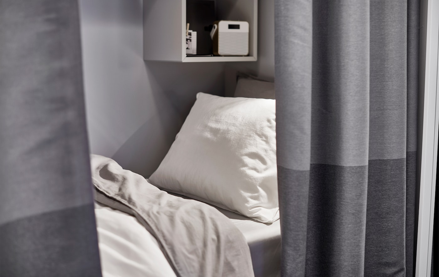 A small bed with a white pillow and light grey bedlinens peeking out from behind a dark grey curtain room divider.