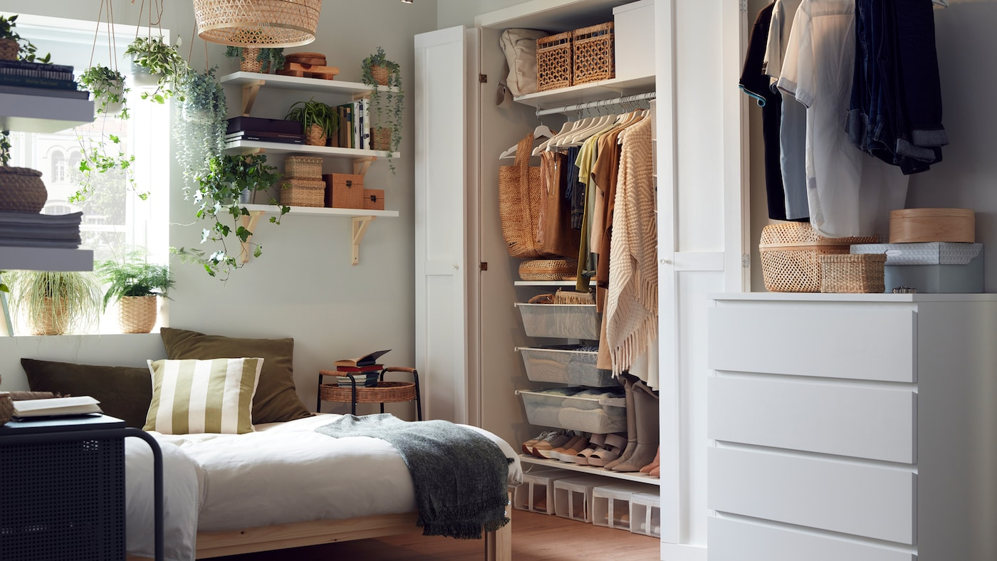 A small bedroom with a wooden bed frame, a wardrobe system with neatly organised clothes, shelves with boxes and plants.