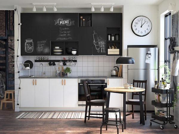 A small black and white styled kitchen with black UDDEVALLA chalk doors as kitchen cabinets inscribed with messages.