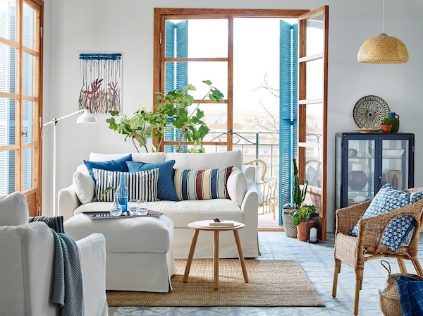 A small blue and white living room with a traditional FÄRLÖV 2-seat sofa in white in the centre. The balcony door is open behind.